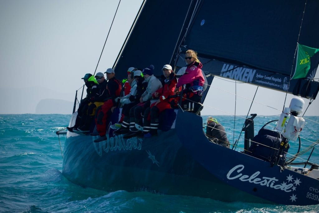 The crew of one of the Sydney to Hobart yachts sitting on the side of the boat, heading down towards Tasman Island.